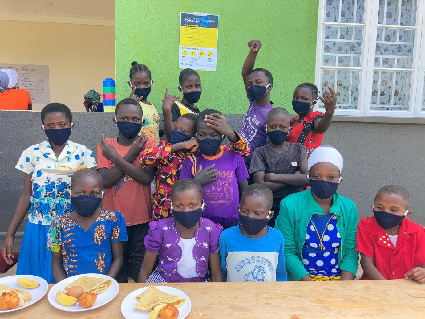 Children putting on masks donated by REFLECT Project during the dissemination exercise at Kyaka II, Kyegegwa district in South Western
